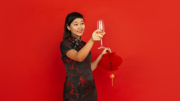 Młoda azjatykcia kobieta pije szampana i trzyma lampion