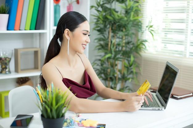 Młoda azjatykcia kobieta płaci z kredytową kartą