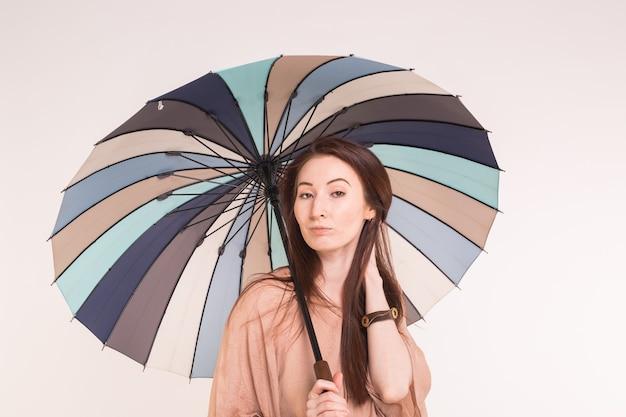 Młoda azjatykcia kobieta pod kolorowym parasolem na białej ścianie
