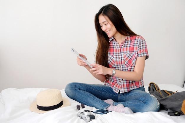 Młoda azjatykcia kobieta podróżnika mienia mapa podczas gdy siedzący na łóżku