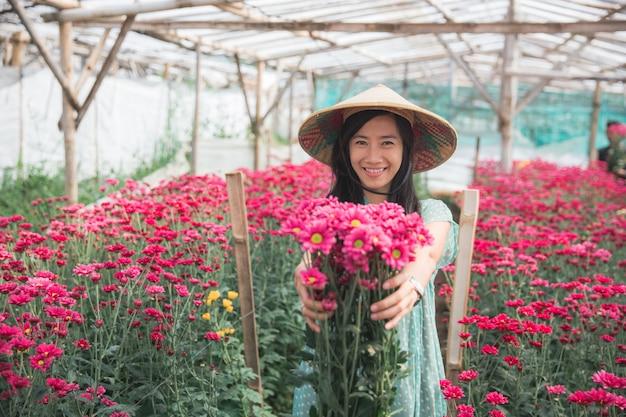 Młoda azjatykcia kobieta pokazuje chamomile kwiaty