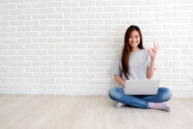 Młoda azjatykcia kobieta pokazuje ok ręka znaka i ono uśmiecha się podczas gdy pracujący z laptopem w białym pokoju