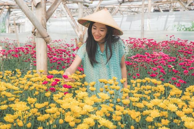 Młoda azjatykcia kobieta pracuje w rumianku kwiatów gospodarstwie rolnym