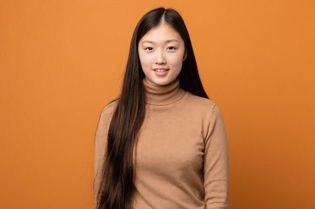 Młoda azjatykcia kobieta przeciw pomarańczowemu tłu