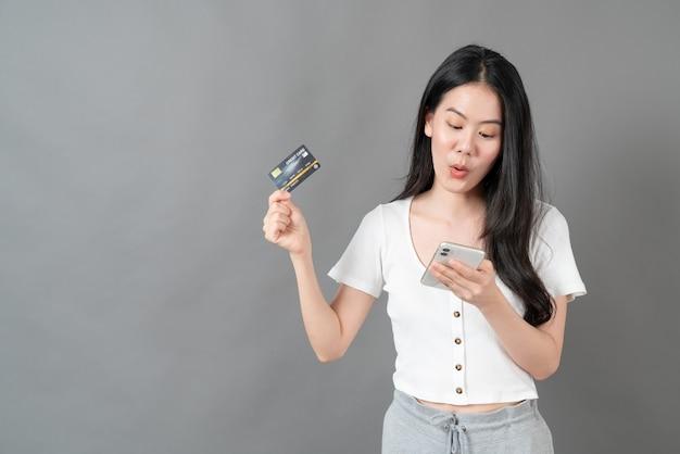 Młoda azjatykcia kobieta przy użyciu telefonu ręką trzymającą kartę kredytową