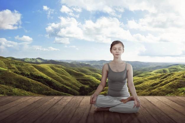Młoda azjatykcia kobieta robi joga lotosowej medytaci na drewnianej podłoga