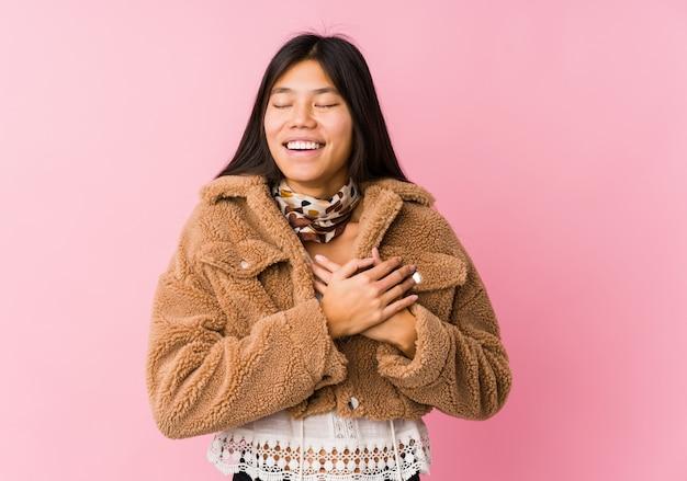 Młoda azjatykcia kobieta śmia się utrzymujący ręki na sercu, pojęcie szczęście.