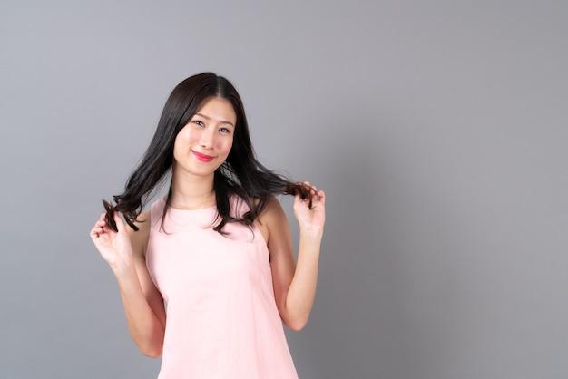 Młoda azjatykcia kobieta szczęśliwa uśmiechając się w różowej sukience na szarej ścianie