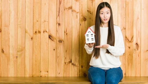 Młoda azjatykcia kobieta trzyma domową ikonę imponującą mienie kopii przestrzeń na palmie.