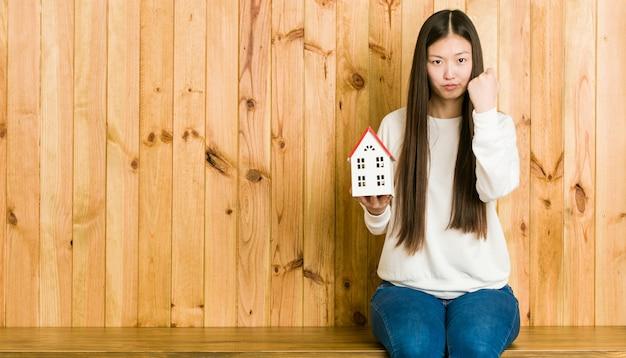 Młoda azjatykcia kobieta trzyma domową ikonę pokazuje pięść kamera, agresywny wyraz twarzy.