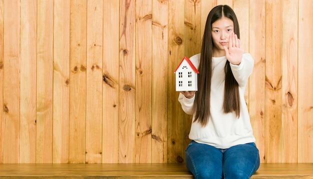 Młoda azjatykcia kobieta trzyma domową pozycję z szeroko rozpościerać ręka seansu przerwy znakiem, zapobiega ciebie.