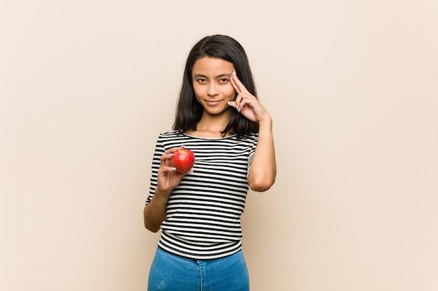 Młoda azjatykcia kobieta trzyma jabłko wskazując palcem świątynię, myśląc, koncentrując się na zadaniu.