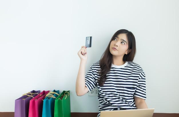 Młoda azjatykcia kobieta trzyma kredytową kartę z jej laptopem i torba na zakupy. zakupy online