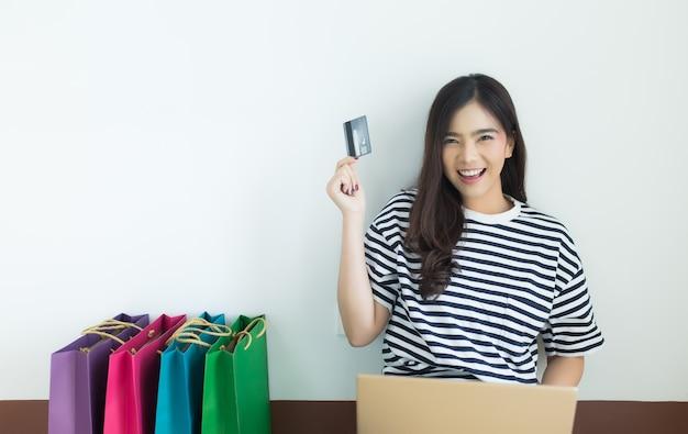 Młoda azjatykcia kobieta trzyma kredytową kartę z jej laptopem i torba na zakupy.