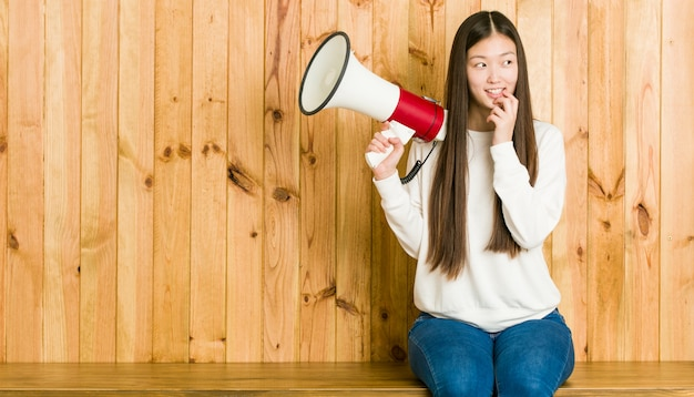Młoda azjatykcia kobieta trzyma megafon relaksował główkowanie o coś patrzeje odbitkową przestrzeń.