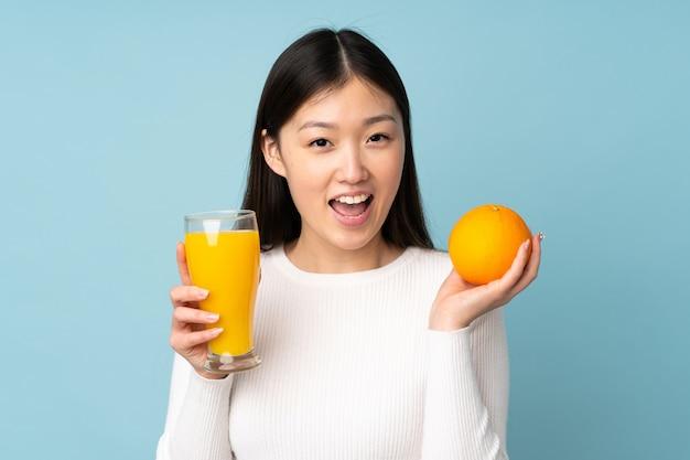 Młoda azjatykcia kobieta trzyma pomarańcze nad odosobnioną błękit przestrzenią