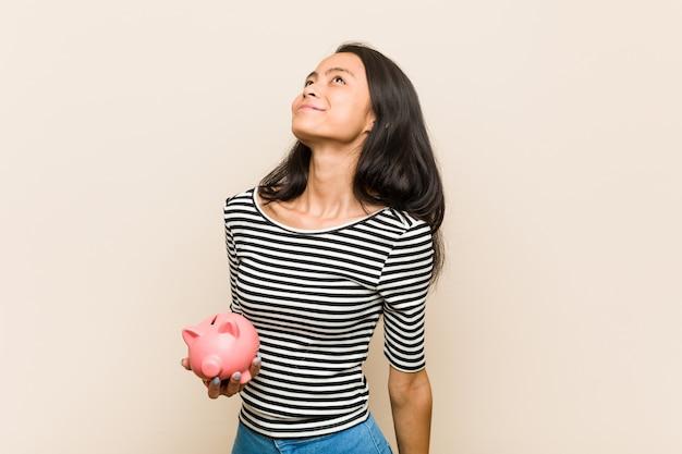 Młoda azjatykcia kobieta trzyma prosiątko banka marzy osiągać cele i zamierzenia