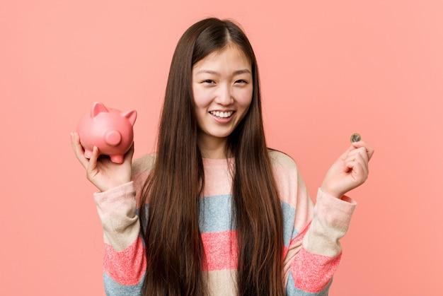 Młoda azjatykcia kobieta trzyma prosiątko banka