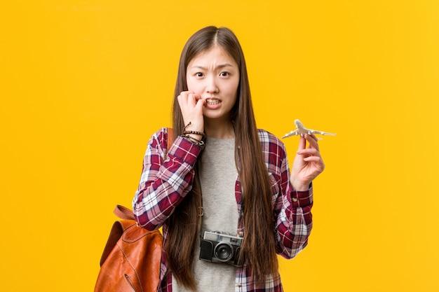 Młoda azjatykcia kobieta trzyma samolotową ikonę gryźć paznokcie, nerwowa i bardzo niespokojna.