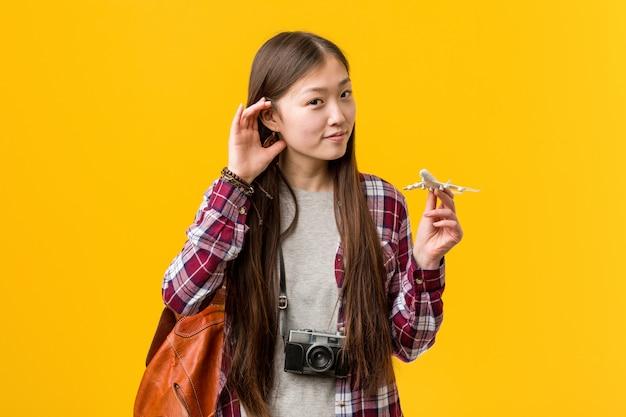 Młoda azjatykcia kobieta trzyma samolotową ikonę próbuje słuchać plotki.