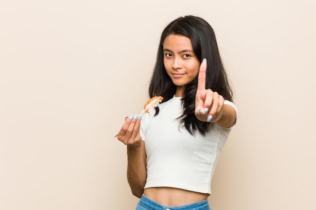 Młoda azjatykcia kobieta trzyma suszi kawałek pokazuje liczbę jeden z palcem.
