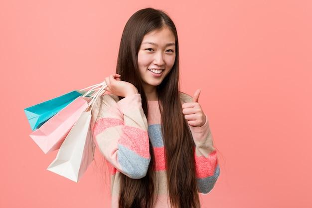 Młoda azjatykcia kobieta trzyma torba na zakupy uśmiecha się kciuk up i podnosi