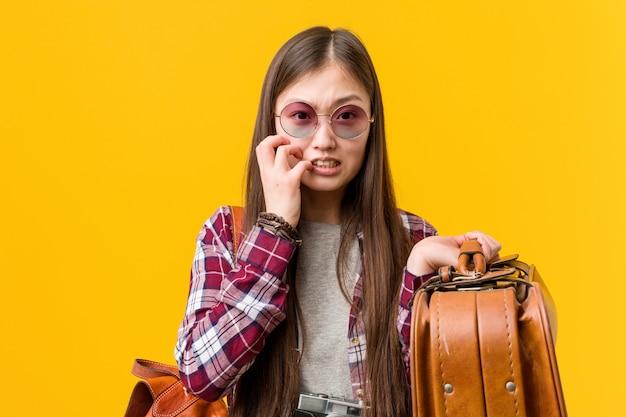 Młoda azjatykcia kobieta trzyma walizkę gryźć paznokcie, nerwowa i bardzo niespokojna.