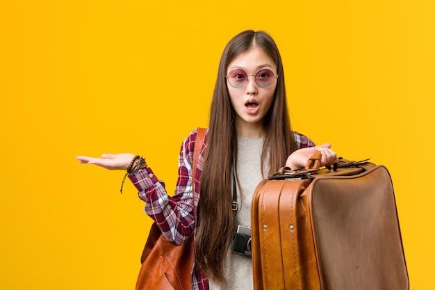 Młoda azjatykcia kobieta trzyma walizkę imponującą mienie kopii przestrzeń na palmie.