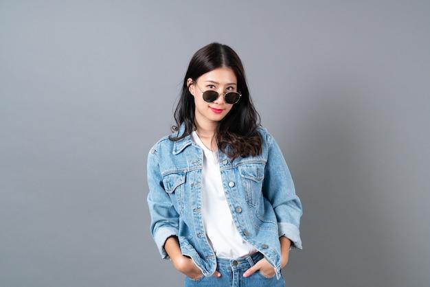 Młoda azjatykcia kobieta ubrana w dżinsy i okulary przeciwsłoneczne na szarej ścianie z miejsca na kopię