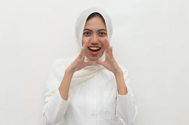 Młoda azjatykcia kobieta ubrana w hidżab wstrząśnięty zakrywając usta rękami za błąd sekretna koncepcja