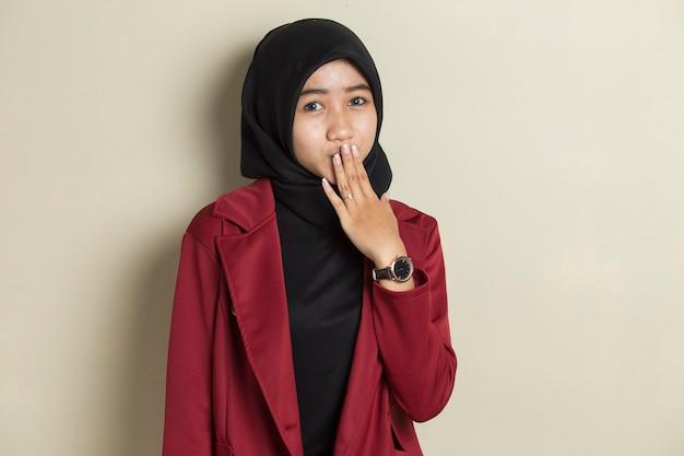 Młoda azjatykcia kobieta ubrana w hidżab wstrząśnięty zakrywając usta rękami za błąd. tajna koncepcja.