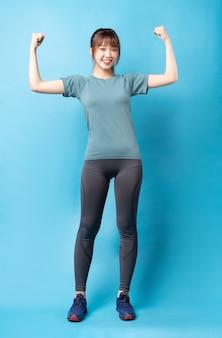 Młoda azjatykcia kobieta ubrana w strój gimnastyczny na niebiesko