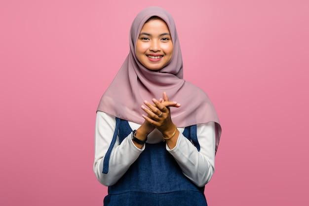 Młoda azjatykcia kobieta uśmiecha się i klaszcze w dłonie