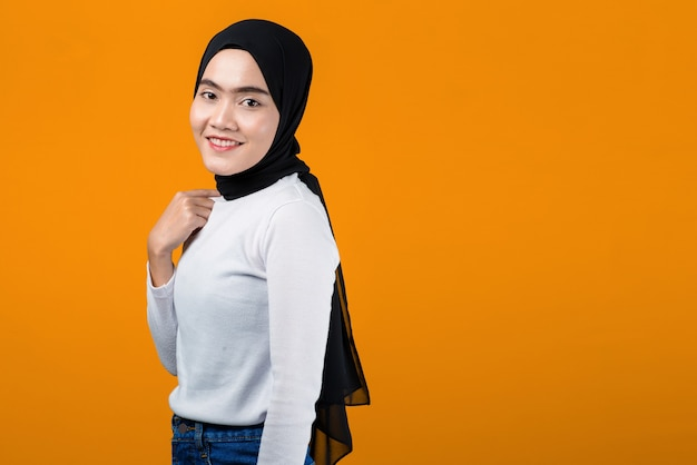 Młoda azjatykcia kobieta uśmiecha się i wygląda na zadowoloną noszenie hidżabu