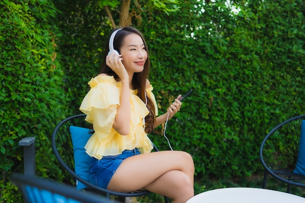 Młoda azjatykcia kobieta używa mądrze telefon komórkowego z hełmofonem dla słucha muzykę wokoło plenerowego ogródu