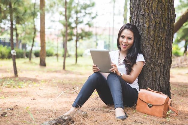 Młoda azjatykcia kobieta używa pastylka komputer osobistego podczas gdy siedzący plenerowy w ap