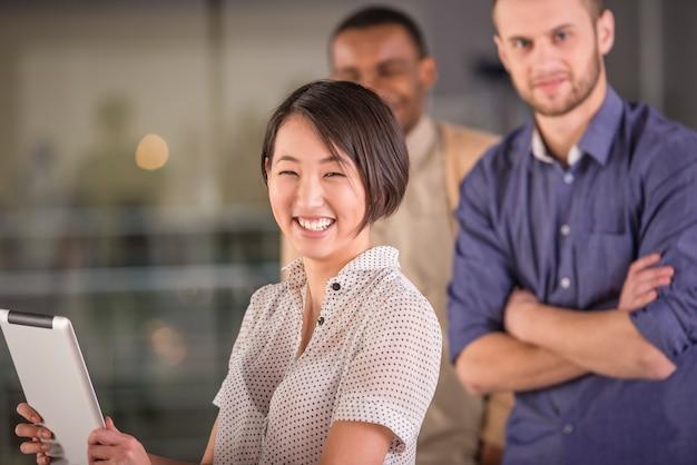 Młoda azjatykcia kobieta używa pastylkę i ono uśmiecha się