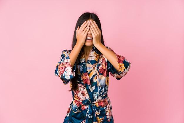 Młoda azjatykcia kobieta w piżamie kimono zakrywa oczy dłońmi, uśmiecha się szeroko czekając na niespodziankę.