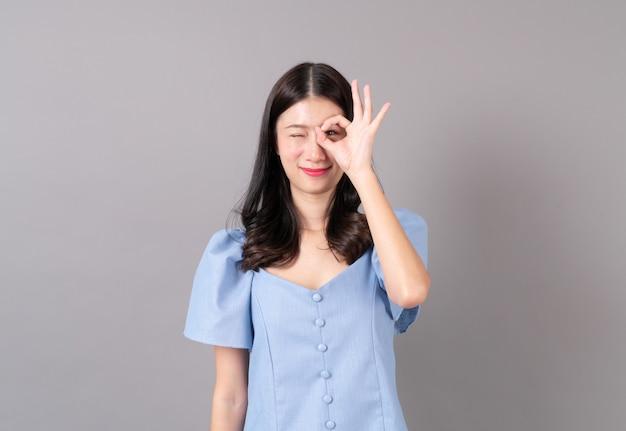 Młoda azjatykcia kobieta w porządku ręka podpisuje niebieską sukienkę na szaro
