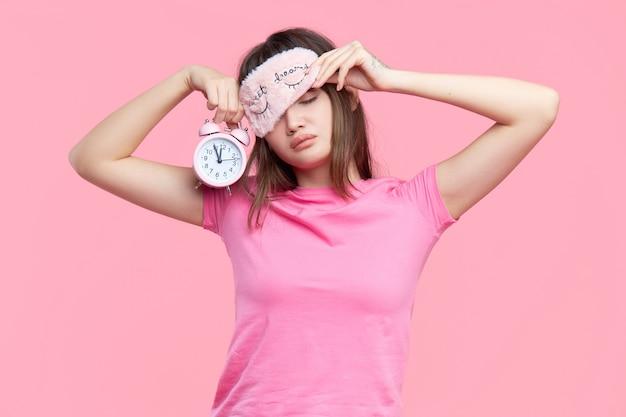 Młoda azjatykcia kobieta w sypialnej oko masce ziewa budzika odizolowywającego na menchiach i trzyma. bezsenna noc
