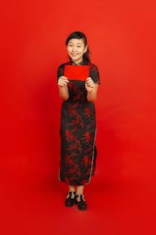 Młoda azjatykcia kobieta z czerwoną kopertą na białym tle na czerwonej ścianie