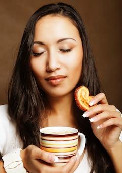 Młoda azjatykcia kobieta z kawą i ciastkami.