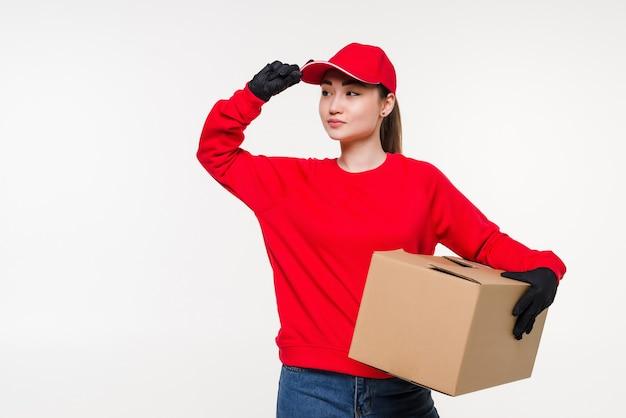 Młoda azjatykcia kobieta z pracownikiem firmy kurierskiej w mundurze. kobieta trzyma pudełko z atrakcyjnym uśmiechem na białym tle.