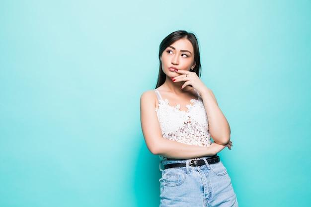 Młoda azjatykcia kobieta z rękami blisko stawia czoło odosobnionego na zieleni ścianie