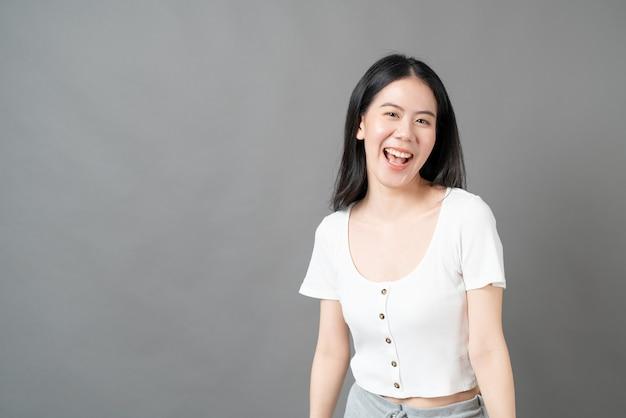 Młoda azjatykcia kobieta z szczęśliwą i uśmiechniętą twarzą w białej koszuli na szarej ścianie