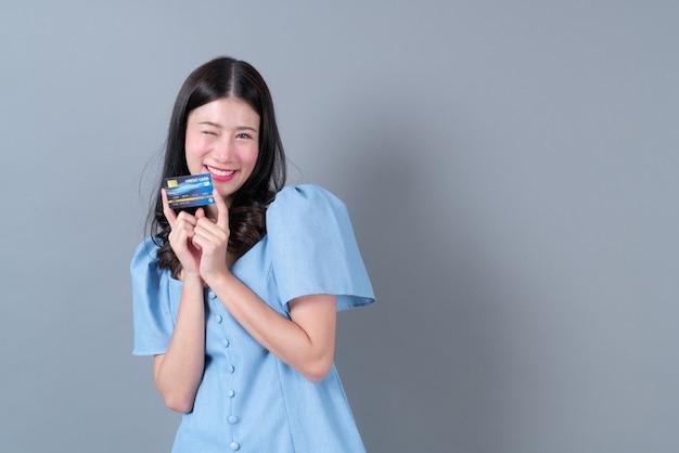 Młoda azjatykcia kobieta z szczęśliwą twarzą i ręką trzymającą kartę kredytową w niebieskiej sukience na szaro