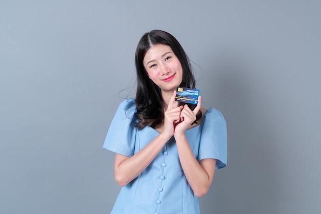 Młoda azjatykcia kobieta z szczęśliwą twarzą i ręką trzymającą kartę kredytową