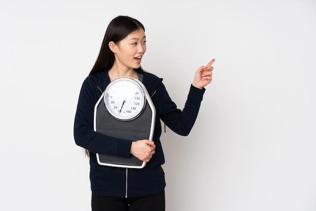 Młoda azjatykcia kobieta z wagą i wskazującą stroną