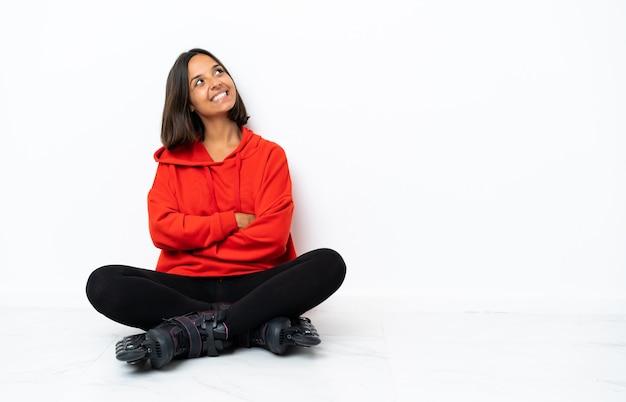 Młoda azjatykcia kobieta z wrotek na podłodze patrząc uśmiechnięty