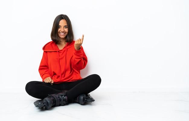 Młoda azjatykcia kobieta z wrotkami na podłodze robi nadchodzący gest